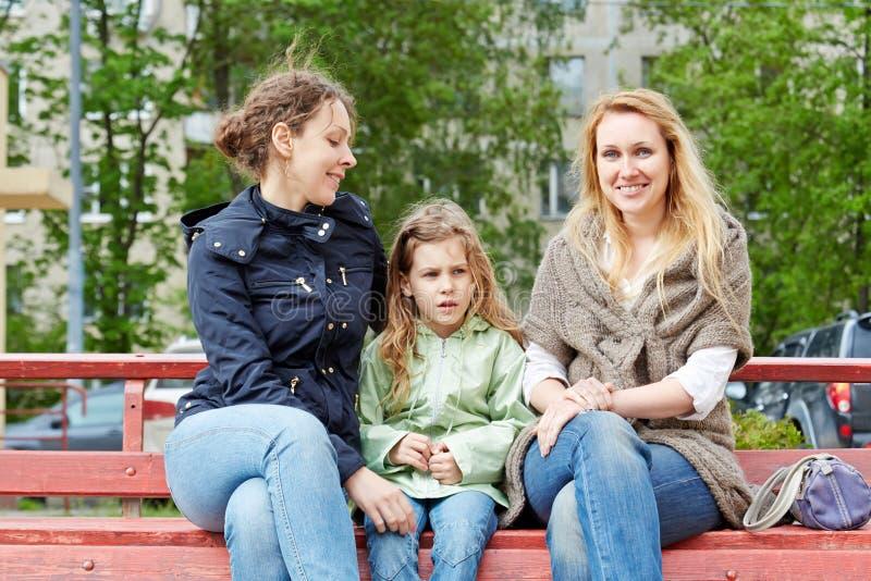 两名妇女和小女孩坐长凳 免版税库存照片
