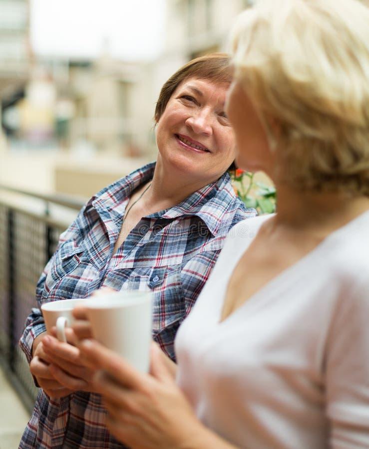 两名妇女在阳台的饮料茶 免版税库存图片