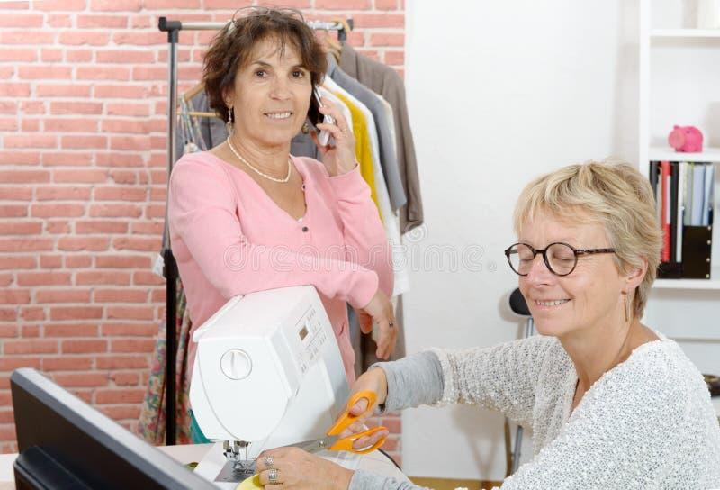 两名妇女工作在一个缝合的车间 库存照片