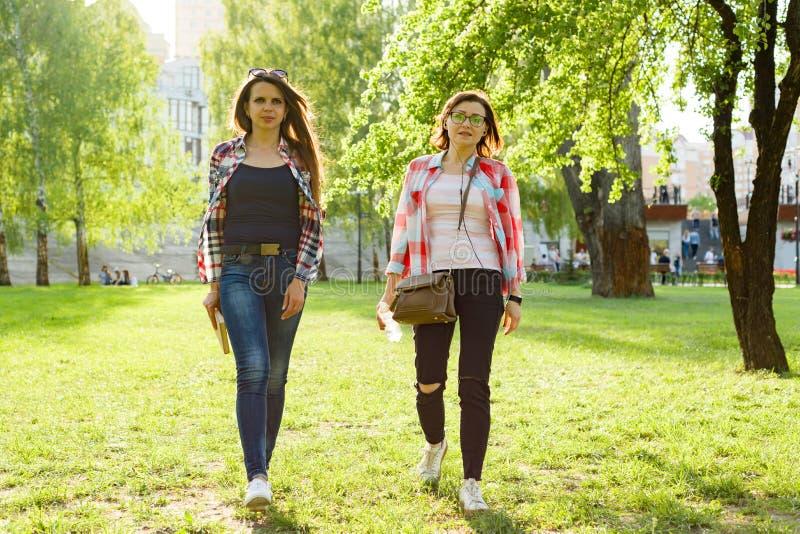 两名妇女步行通过城市公园 库存图片