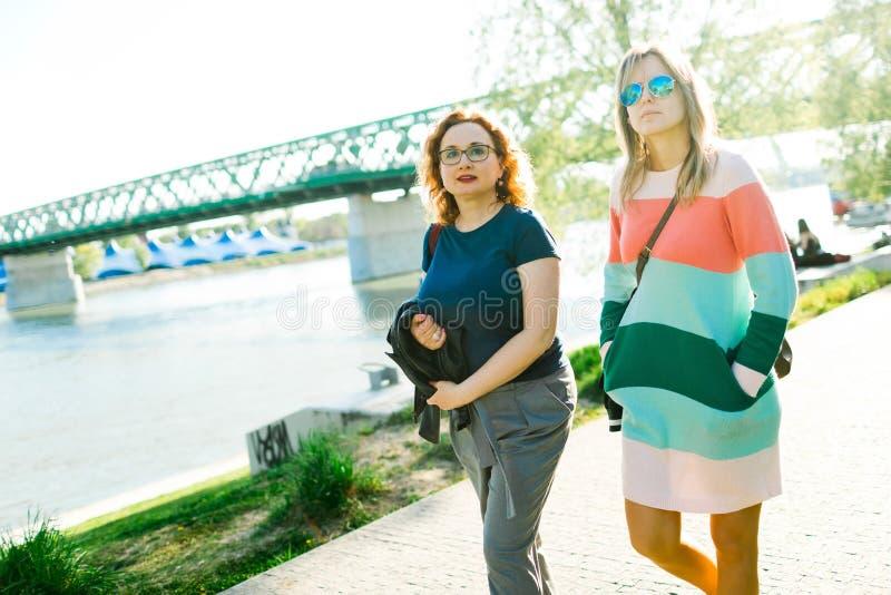 两名妇女走沿江边的-桥梁在背景中 免版税库存照片
