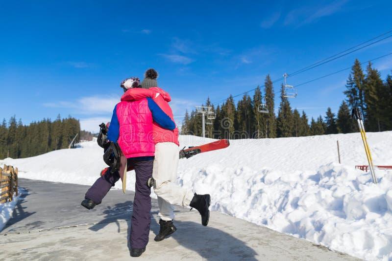 两名妇女滑雪和雪板手段冬天雪山激动的女孩容忍假日 免版税图库摄影