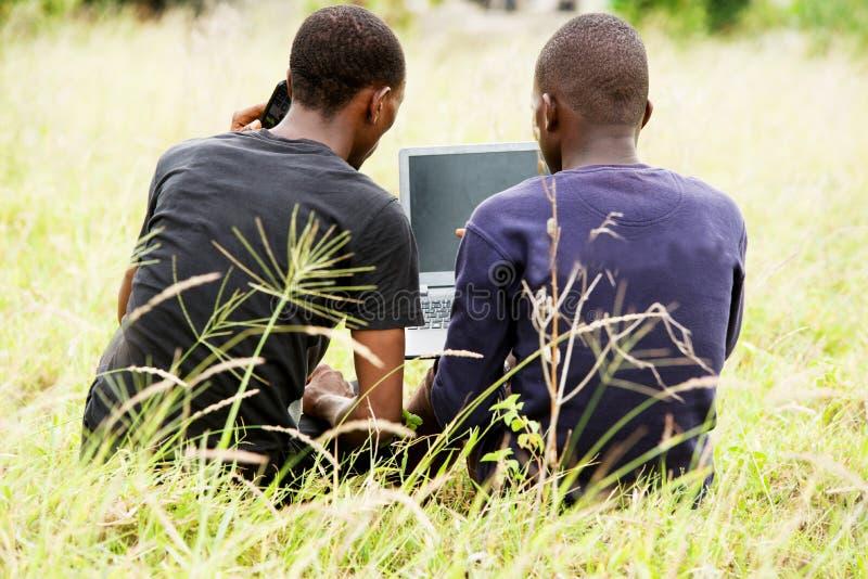 两名学生一起研究膝上型计算机在公园 库存照片