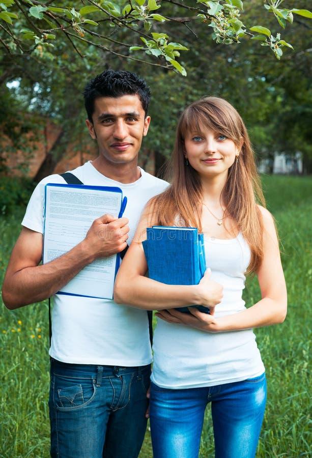 两名学生在有户外书的公园 免版税库存图片