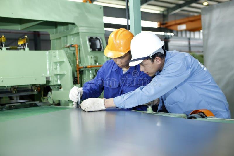 两名工作者在一个机械车间工作 免版税库存照片