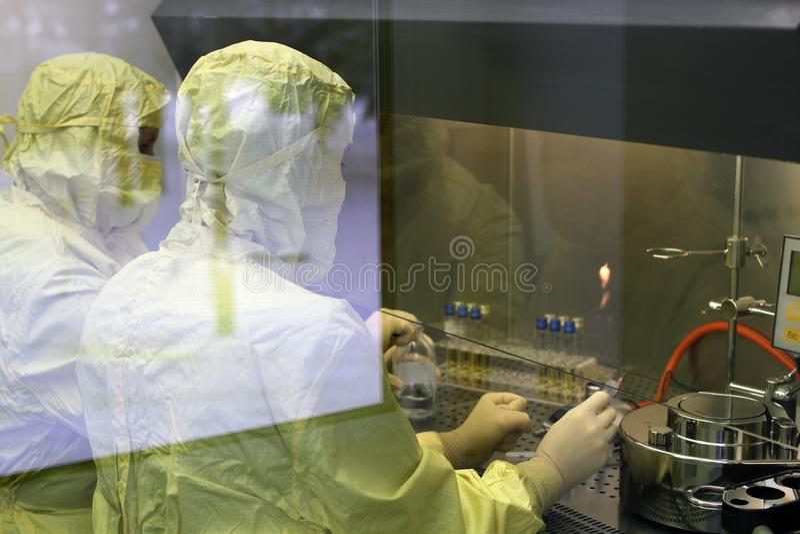 两名工作者在一个防护服装实验室进行研究 免版税库存图片