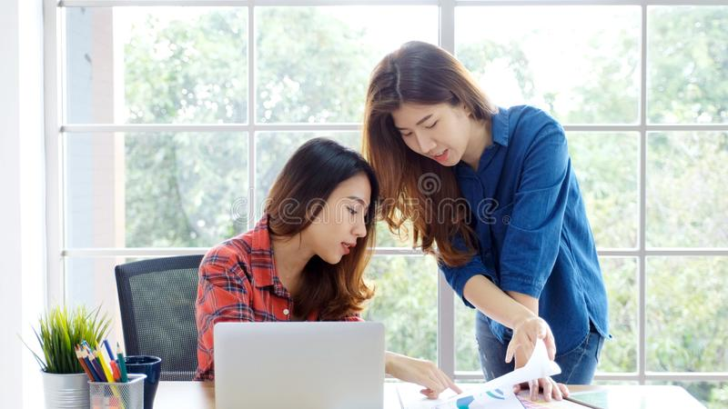 两名年轻亚裔妇女在家与有愉快的情感片刻的手提电脑办公室一起使用,在家运作,小企业, 库存照片