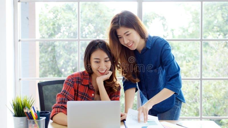 两名年轻亚裔妇女在家与有愉快的情感片刻的手提电脑办公室一起使用,在家运作,小企业, 免版税库存照片