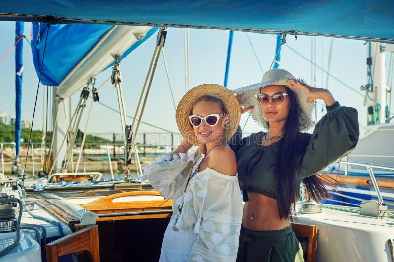 两名年轻可爱的妇女基于一条游艇在一个晴天 图库摄影