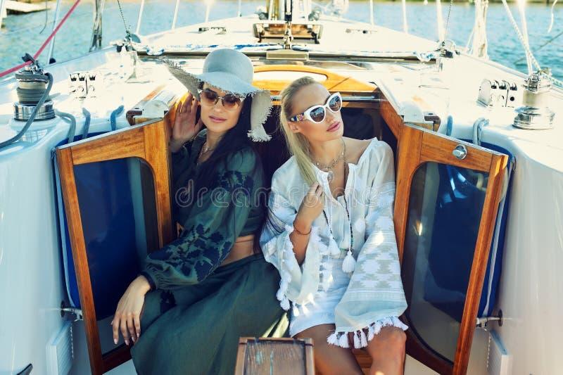 两名年轻可爱的妇女基于一条游艇在一个晴天 库存照片