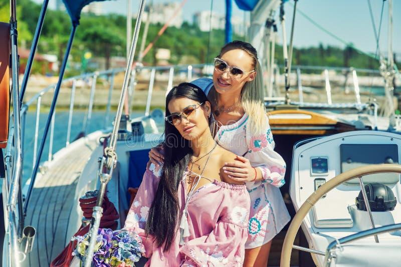 两名年轻可爱的妇女基于一条游艇在一个晴天 免版税图库摄影
