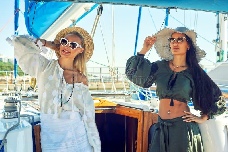 两名年轻可爱的妇女基于一条游艇在一个晴天 免版税库存图片