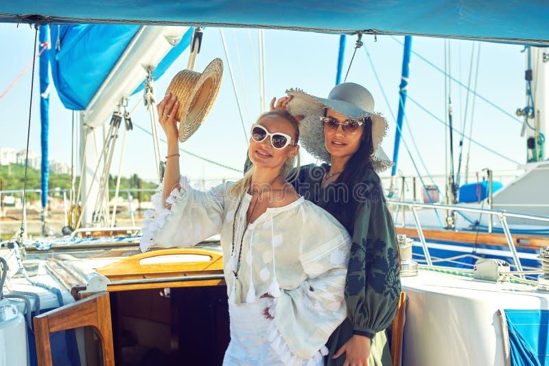 两名年轻可爱的妇女基于一条游艇在一个晴天 库存图片