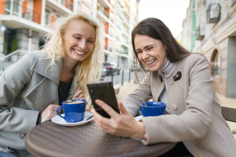 两名年轻微笑的妇女获得乐趣在室外咖啡馆 都市秋天背景 库存图片