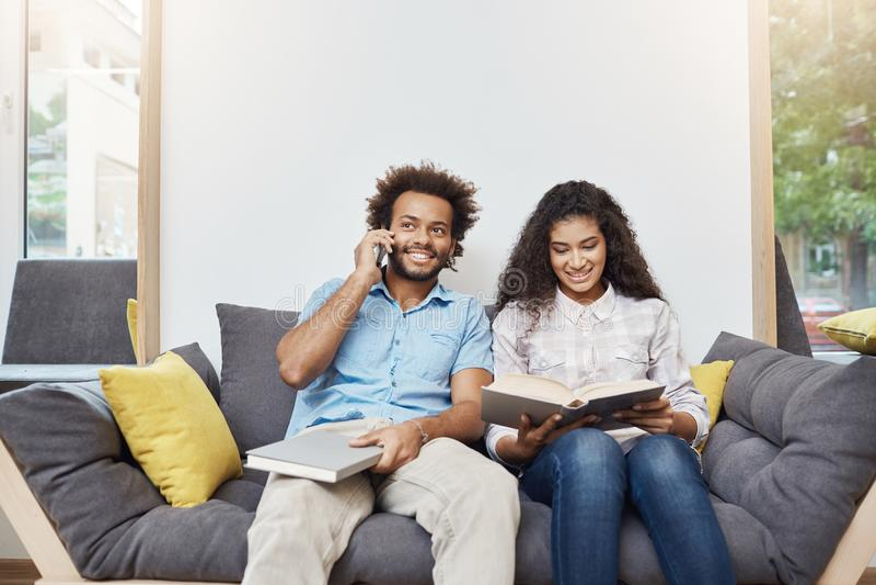两名年轻悦目深色皮肤的学生画象便衣的一起坐沙发在现代图书馆里 图库摄影