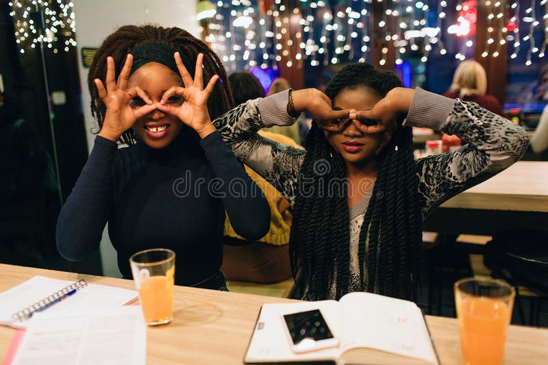 两名年轻非洲妇女一起获得乐趣 他们在眼睛和神色附近握手直接 模型坐在咖啡馆的桌上 免版税库存图片