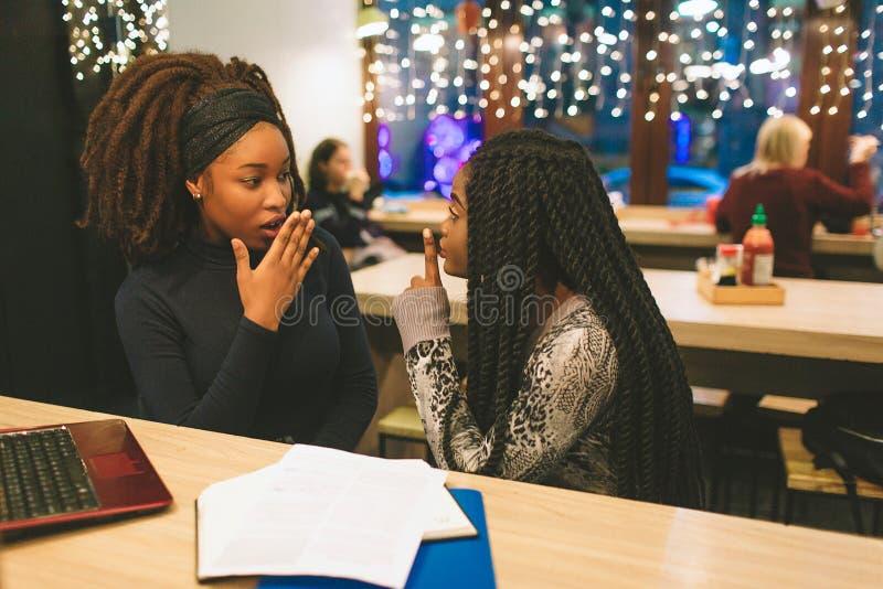 两名年轻非洲妇女闲话在桌上 在他们神色想知道 另一个模型保留手指在嘴 他们有膝上型计算机 免版税库存照片