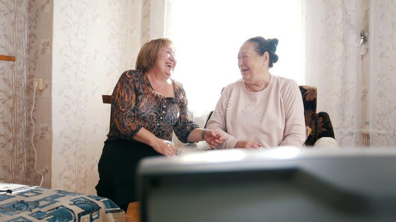 两名年长妇女看着电视,看在彼此和笑 免版税库存照片