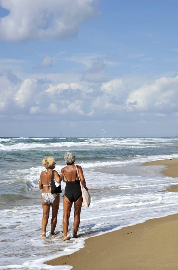 两名年长妇女走和谈话在海滩 免版税库存照片