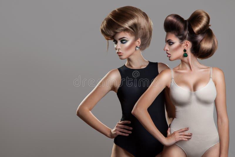 两名性感的妇女水平的画象有创造性的发型的 库存照片