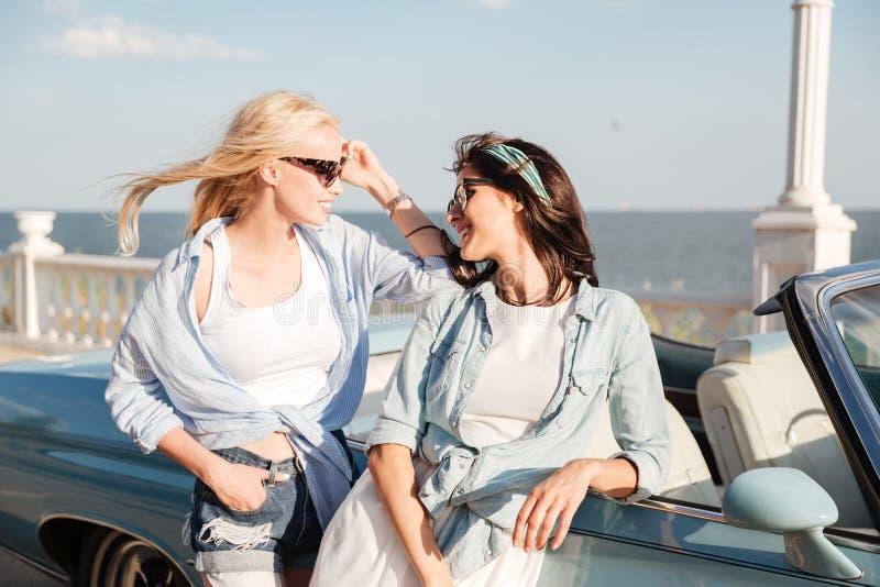 两名愉快的妇女站立和谈话在敞蓬车附近 免版税库存照片