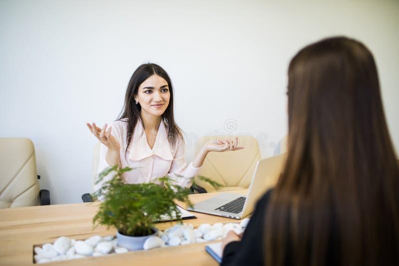 两名成功的女实业家坐在书桌和谈话在工作 图库摄影
