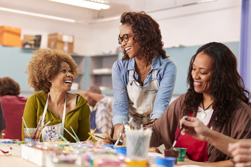 两名成熟妇女在社区活动中心的上艺术课与老师 库存图片