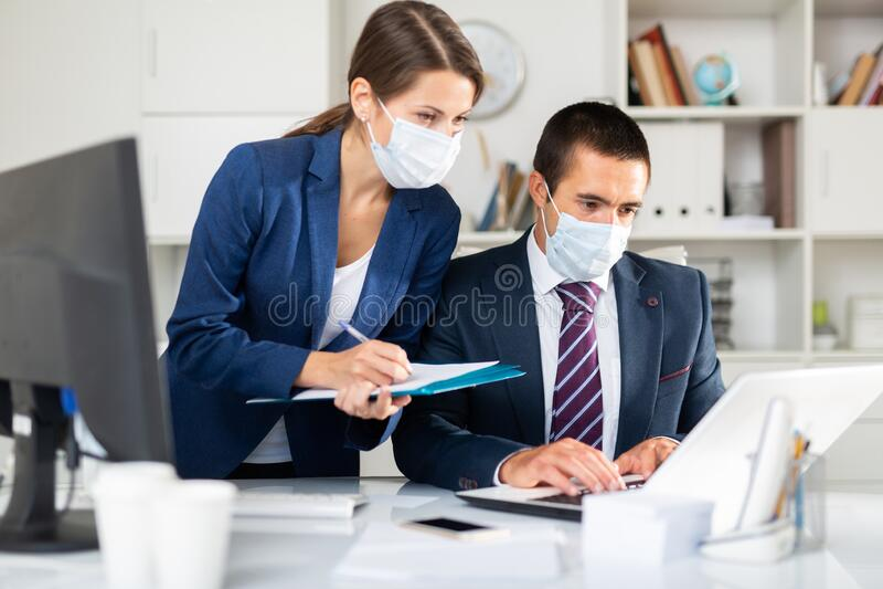 两名戴医用口罩的员工在办公室工作 免版税库存照片