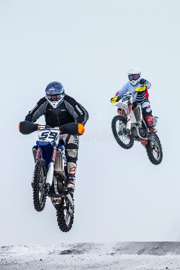两名摩托车骑士在飞行中在跳跃从小山以后 免版税库存图片