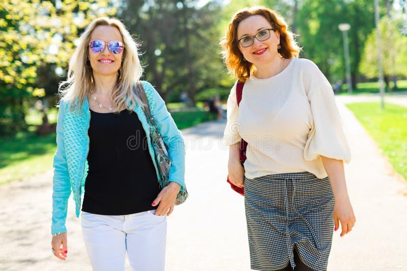 两名有吸引力妇女走街市和谈论 免版税库存照片