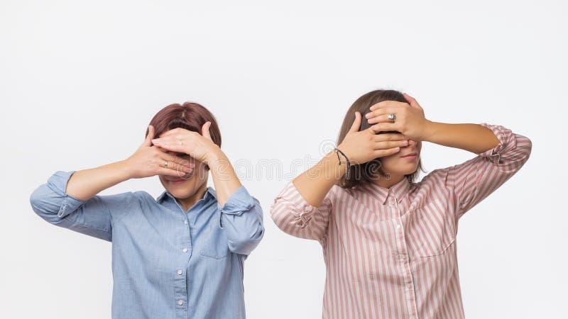 两名欧洲妇女盖他们的面孔的母亲和女儿使用手 免版税库存图片