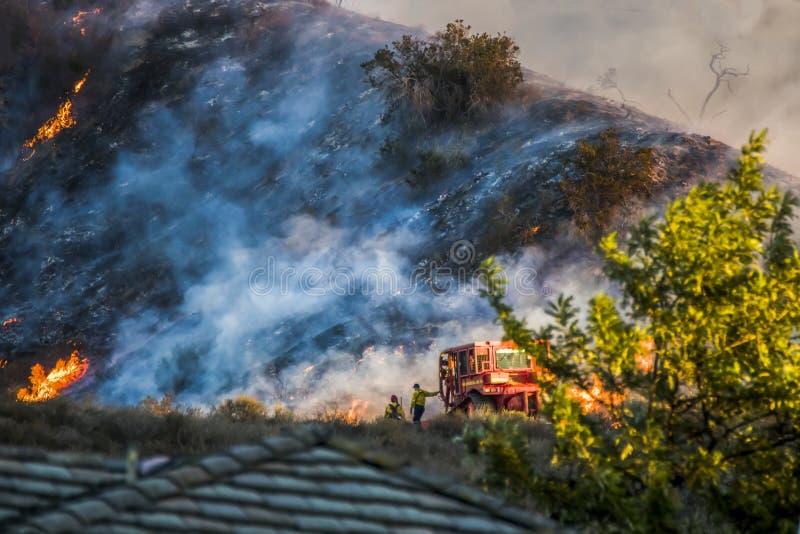 两名消防队员在有烧在背景中的山坡的推土机旁边站立在加利福尼亚火期间 免版税库存照片
