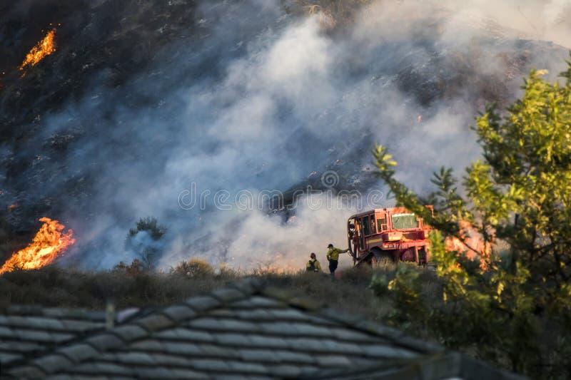 两名消防队员支持有烧在背景中的小山的推土机 免版税库存照片