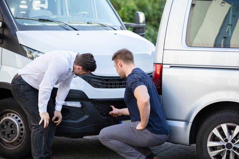 两名男子在检查车辆事故后损坏 免版税库存图片