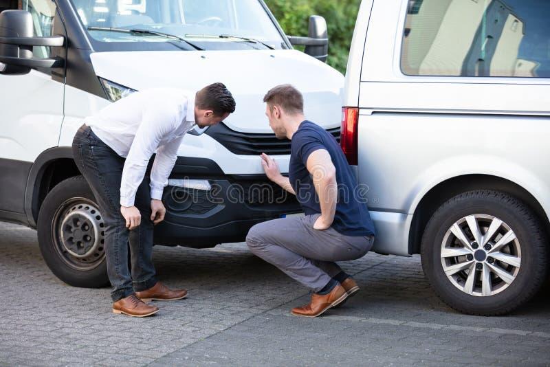 两名男子在检查车辆事故后损坏 库存照片