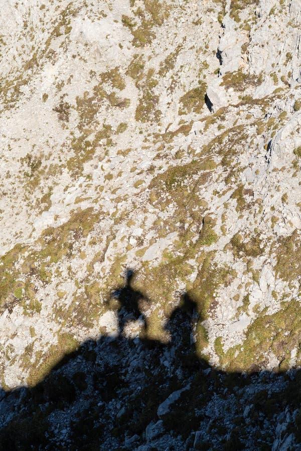 两名登山家的阴影在山顶部的 库存照片