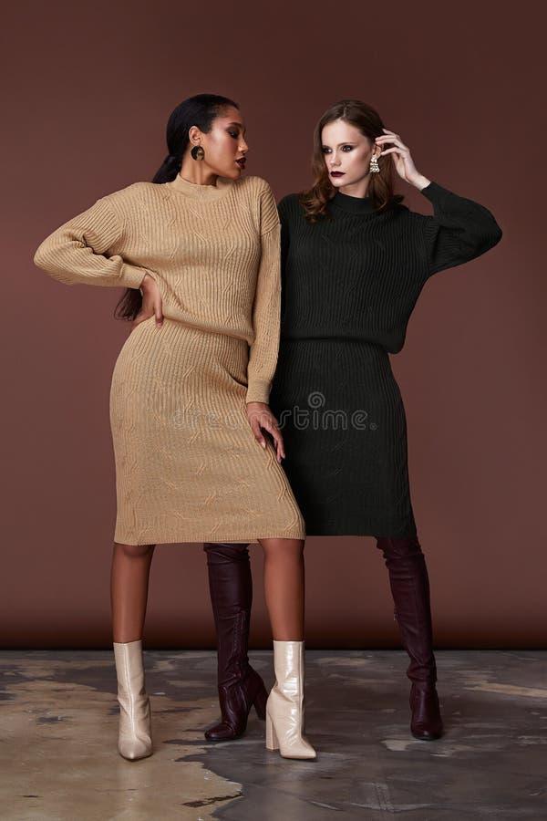 两名秀丽妇女相当面对穿米黄和绿色被编织的衣服身材构成化妆辅助袋子汇集鞋子 库存照片