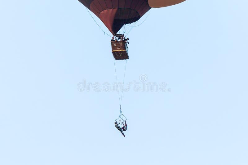 两名空中杂技演员显示在从一个热空气气球暂停的秋千的表现在热空气气球节日 库存照片