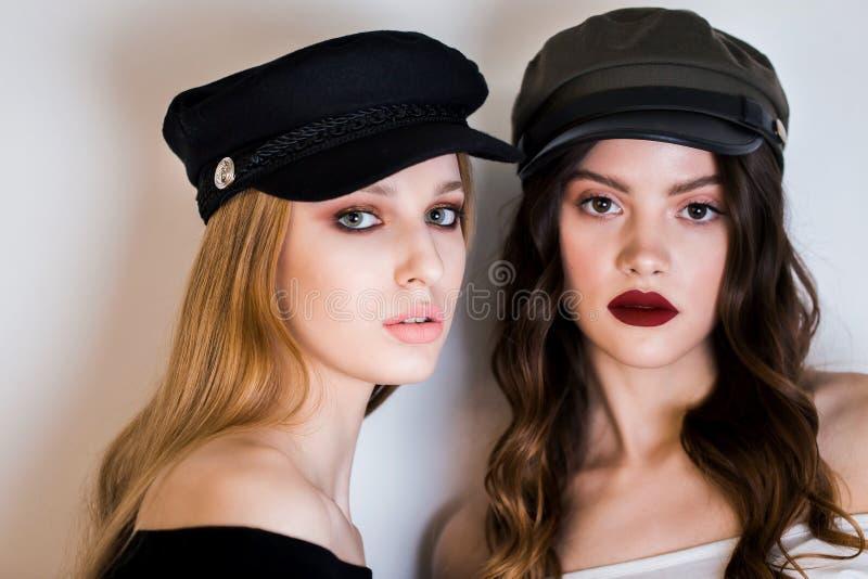两名美丽的妇女、女朋友、金发碧眼的女人和浅黑肤色的男人女孩黑盖帽的和明亮的构成看照相机在一白色backgrou 库存照片