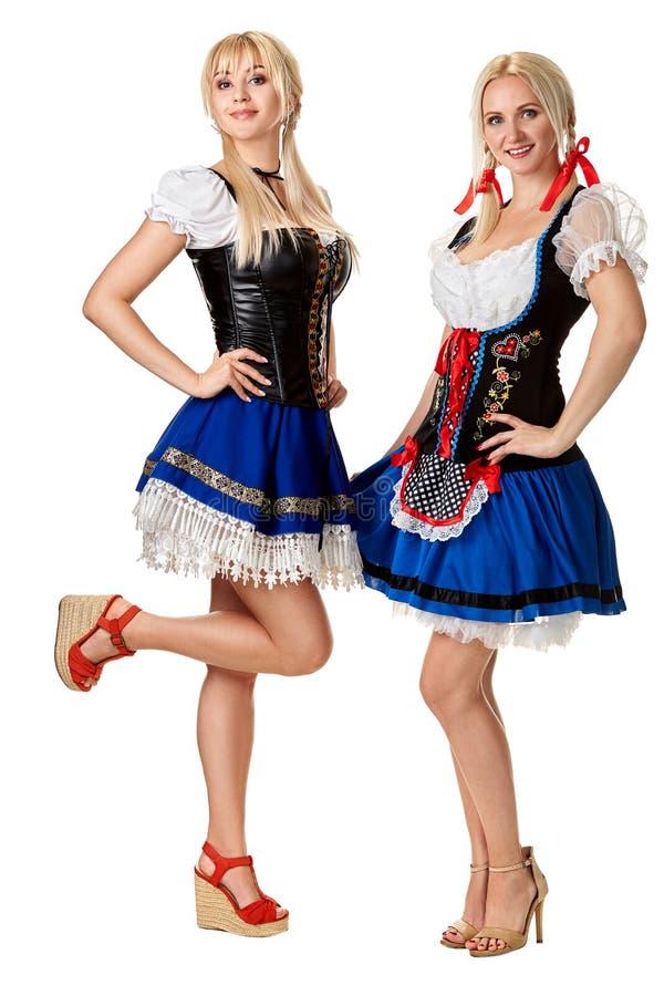 两名美丽的妇女一张全长画象在白色隔绝的一套传统服装的 oktoberfest 免版税库存照片