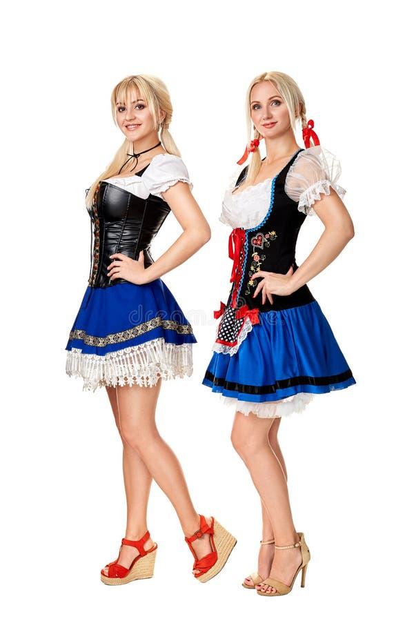 两名美丽的妇女一张全长画象在白色隔绝的一套传统服装的 oktoberfest 免版税库存图片