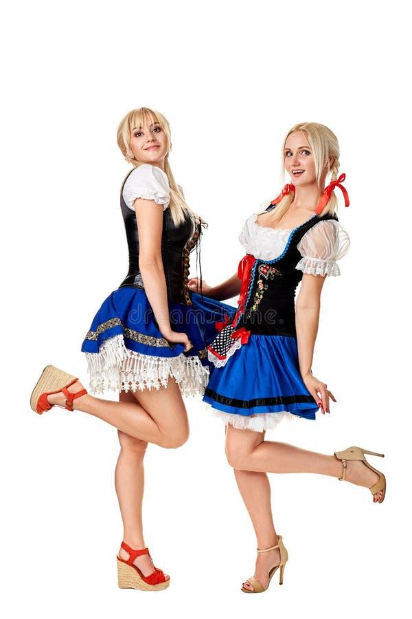 两名美丽的妇女一张全长画象在白色隔绝的一套传统服装的 oktoberfest 库存照片