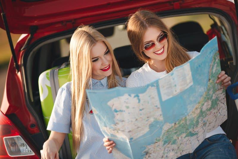 两名美丽的妇女在一辆红色汽车旅行 免版税库存照片