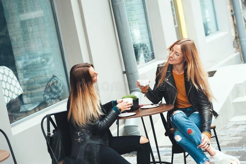 两名美丽的年轻白肤金发的妇女喝咖啡和说闲话在室外好的餐馆 免版税库存照片