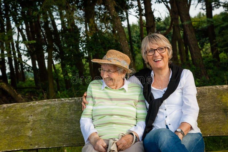 两名资深妇女坐一条长凳在公园,概念世代,家庭,关心 库存图片