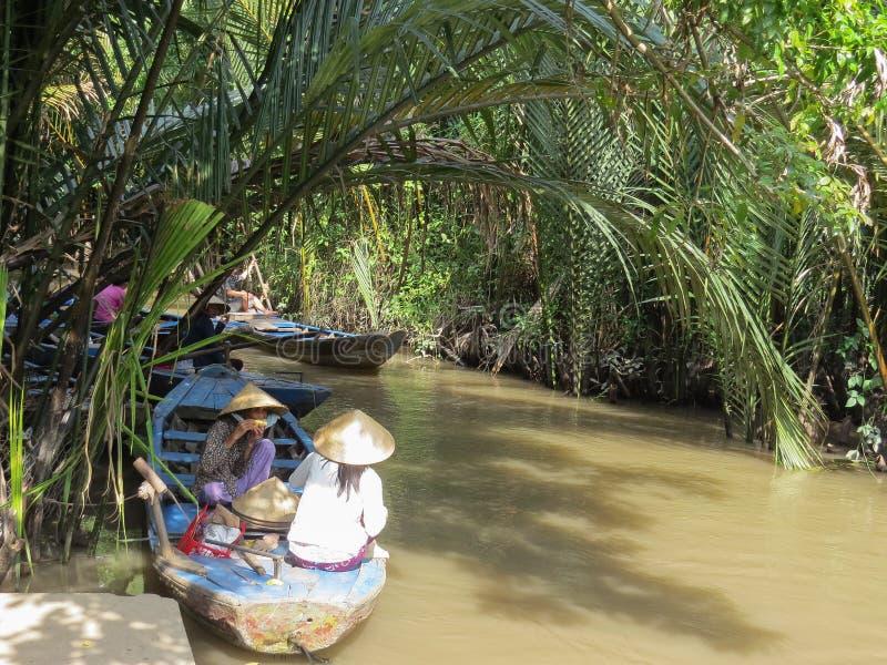 两名越南妇女吃坐的午餐在一条木小船 湄公河的狭窄的三角洲 库存图片