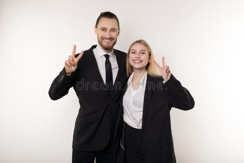 两名雇员在工作周末愉快地笑,显示viktory标志和看照相机 库存照片