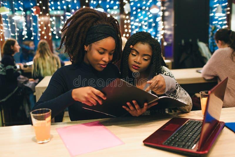 两名非洲学生看被打开的学报 他们坐并且学习 他们有在桌上的红色膝上型计算机 库存照片
