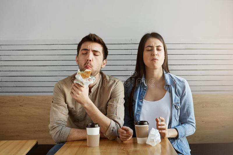 两名饥饿的学生在一长的困难的日子研究以后有膳食在自助食堂 吃与大的年轻对三明治 免版税库存图片