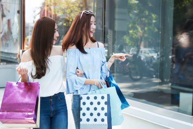 两名年轻愉快的亚裔妇女购物的室外商城 库存图片
